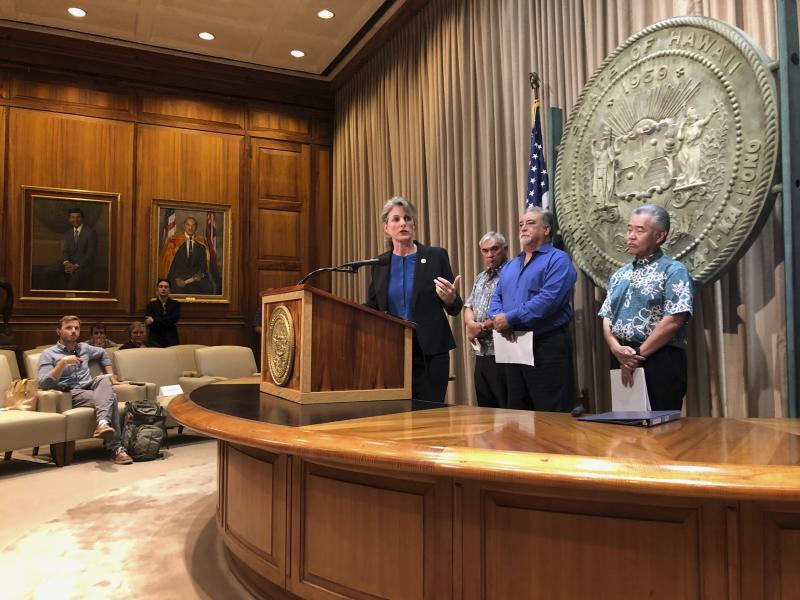 Hawaii Attorney General Clare Connors talks to reporters in Honolulu on Friday, Sept. 13, 2019 about threats state employees have received amid the heated debate over building a giant telescope on the state's highest peak. Behind her are Department of Hawaiian Homelands Director William Aila Jr., left, Department of Public Safety Director Nola Espinda, middle, and Gov. David Ige. (AP Photo/Jennifer Sinco Kelleher)