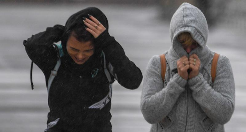 Commuters are seen as winter weather and large surf lashes Bondi Beach, in Sydney.