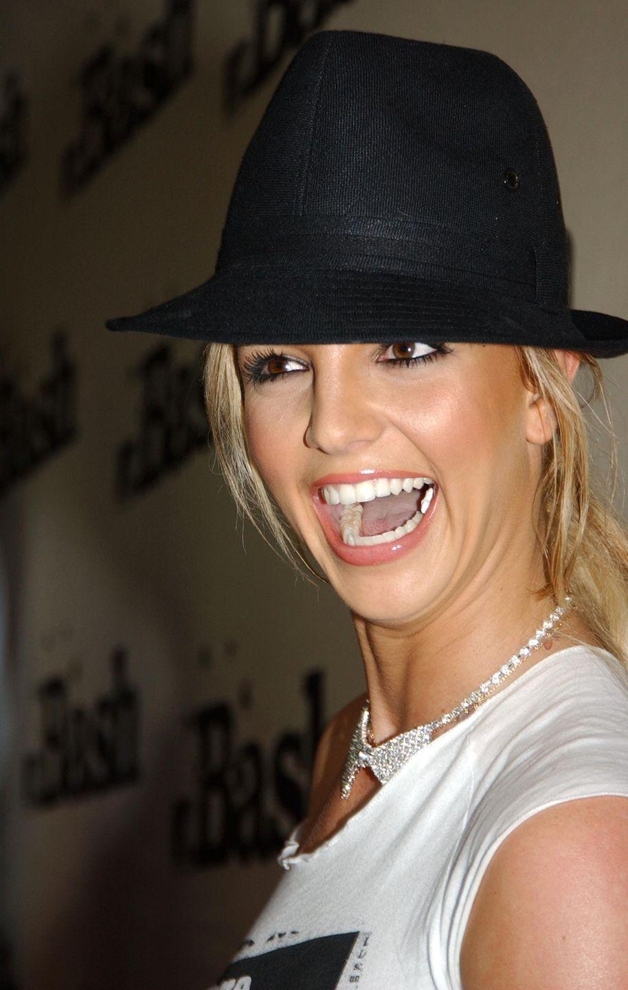 <p>Have you ever seen a more glorious fedora? Also, peep the rhinestone bow-tie necklace, the ripped tee, and the piece of gum still in her mouth.</p>