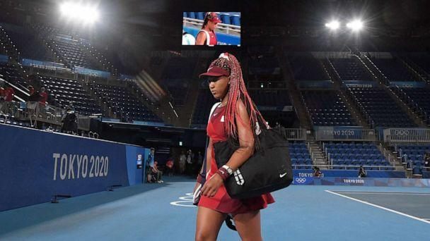 PHOTO: Japan's Naomi Osaka leaves the court after being beaten by Czech Republic's Marketa Vondrousova in their Tokyo 2020 Olympic Games women's singles third round tennis match at the Ariake Tennis Park in Tokyo on July 27, 2021. (Tiziana Fabi/AFP via Getty Images)