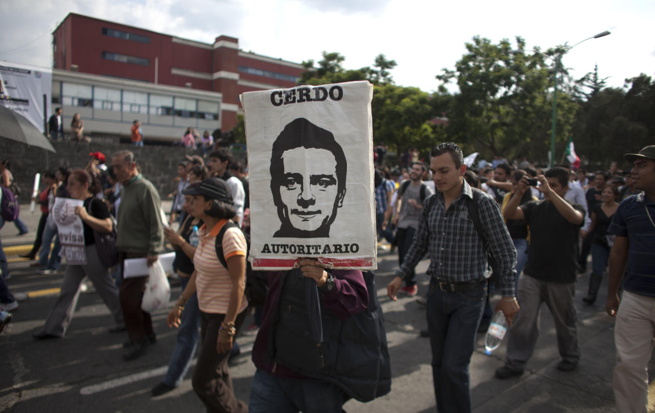"A demonstrator holds an image depicting Mexico's President-elect Enrique Pena Nieto, of the Institutional Revolutionary Party (PRI), that reads in Spanish ""Authoritarian pig"" during a protest against the official presidential election results in Mexico City, Friday, Aug. 31, 2012. On Friday, the Federal Electoral Tribunal declared Pena Nieto won the majority of votes in last July's presidential election, and he will be sworn-in on Dec. 1. (AP Photo/Alexandre Meneghini)"