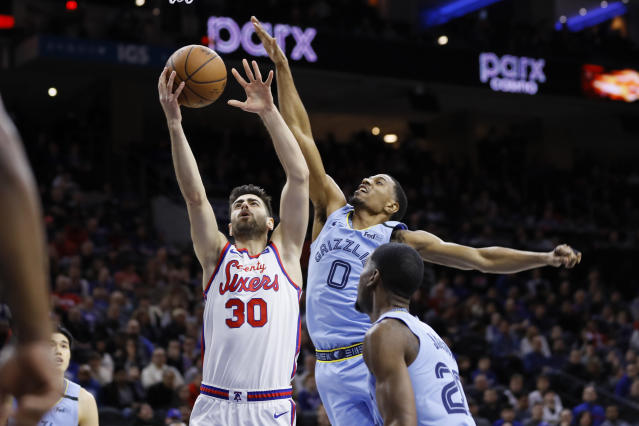 Philadelphia 76ers' Furkan Korkmaz (30) goes up for a shot against Memphis Grizzlies' De'Anthony Melton (0) and Josh Jackson (20) during the first half of an NBA basketball game Friday, Feb. 7, 2020, in Philadelphia. (AP Photo/Matt Slocum)