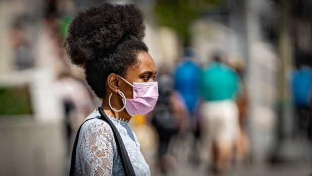 A pedestrian wearing a pink mask walks in downtown Ottawa on Aug. 9, 2021, during the COVID-19 pandemic. (Brian Morris/CBC - image credit)