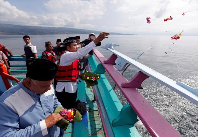 Villagers and Muslim clerics throws flowers after praying for the missing passengers, after a ferry sank earlier this week in Lake Toba in Simalungun, North Sumatra, Indonesia, June 22, 2018. REUTERS/Beawiharta TPX IMAGES OF THE DAY