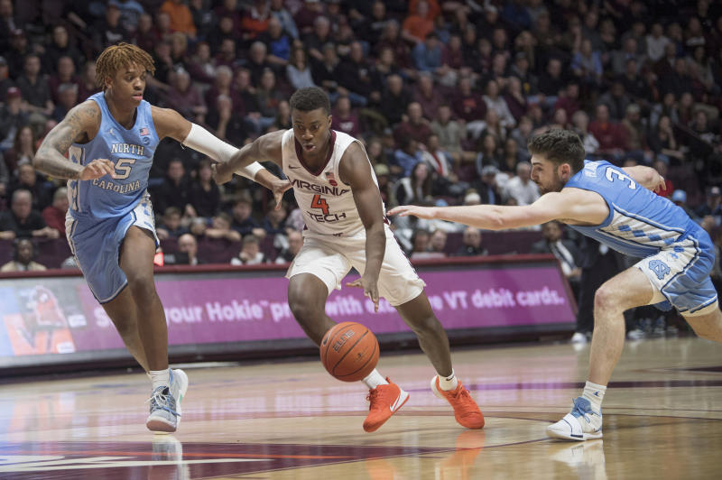 Virginia Tech guard Nahiem Alleyne (4) drives between North Carolina defenders Armando Bacon (5) and Andrew Platek (3) during the second half of an NCAA college basketball game in Blacksburg, Va., Wednesday, Jan. 22, 2020.(AP Photo/Lee Luther Jr.)