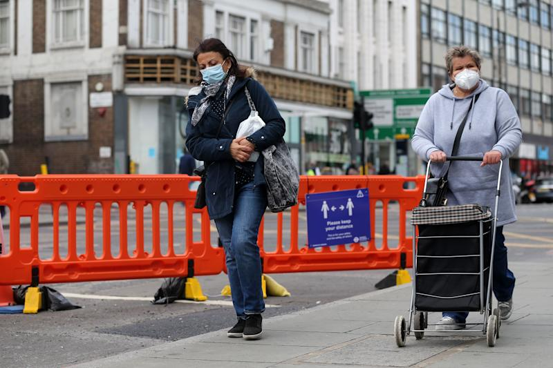 "To women wearing protective face masks walk beside the recently widened pavement on Camden High Street in central London on May 11, 2020, as life in Britain continues during the nationwide lockdown due to the novel coronavirus pandemic. - British Prime Minister Boris Johnson on May 10 announced a phased plan to ease a nationwide coronavirus lockdown, with schools and shops to begin opening from June 1 -- as long as infection rates stay low. Starting this week, he said the government would be ""actively encouraging"" people to return to work where they could not do so from home, for example in manufacturing or construction. (Photo by ISABEL INFANTES / AFP) (Photo by ISABEL INFANTES/AFP via Getty Images)"