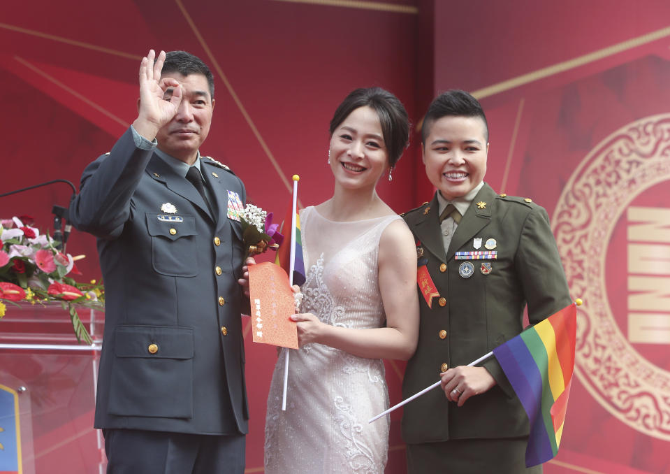 Lesbian couple Yi Wang, right, Yumi Meng and General Chen Pao-Yu pose for a photo during a military mass weddings ceremony in Taoyuan city, northern Taiwan, Friday, Oct. 30, 2020. Two lesbian couples tied the knot in a mass ceremony held by Taiwan's military on Friday in a historic step for the island. Taiwan is the only place in Asia to have legalized gay marriage, passing legislation in this regard in May 2019. (AP Photo/Chiang Ying-ying)