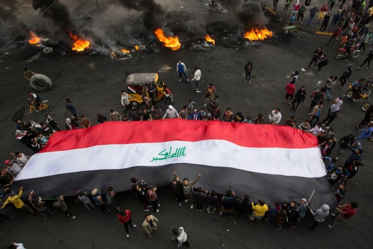 Iraqi demonstrators carry a giant national flag as others burn tyres to cut off roads in the southern city of Basra
