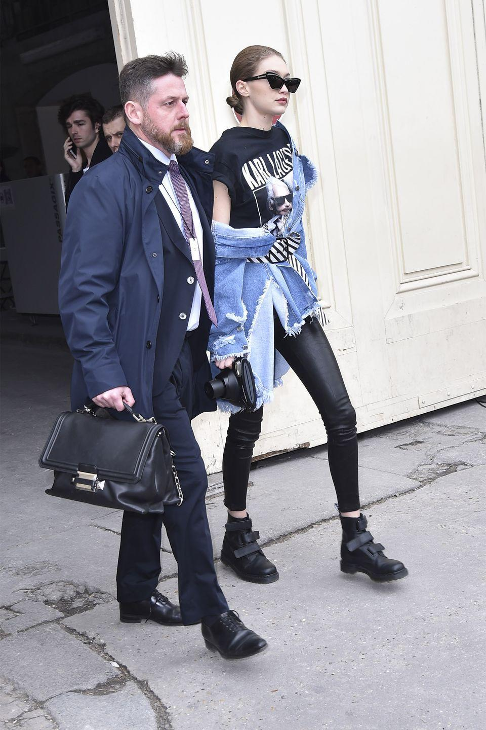 <p>In a graphic tee under an oversized denim jacket tied at the waist with a stripped belt, skinny leather pants and Dr. Martens boots with Karen Walker sunglasses while leaving the Chanel show in Paris. </p>