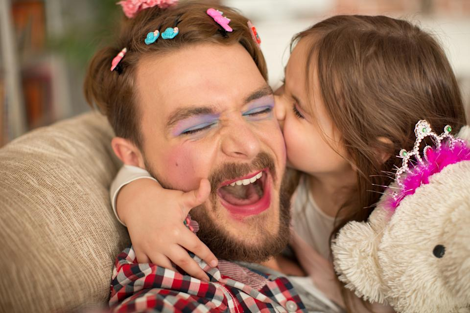 Cute daughter and her father having princess time. Father looks funny, wearing makeup and tiara, holding bear toy wearing tiara too. Girl embracing him and kissing. Bonding time.