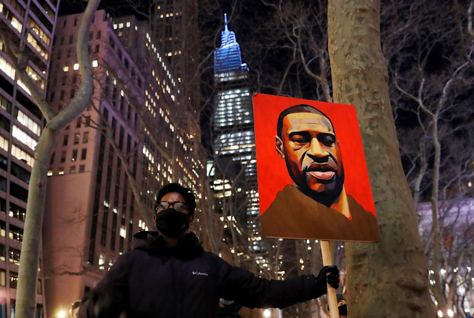 A demonstrator holds up an image of George Floyd during a rally on the first day of the trial of former Minneapolis police officer Derek Chauvin, on murder charges in the death of Floyd, in New York City, New York, U.S., March 8, 2021. REUTERS/Shannon Stapleton