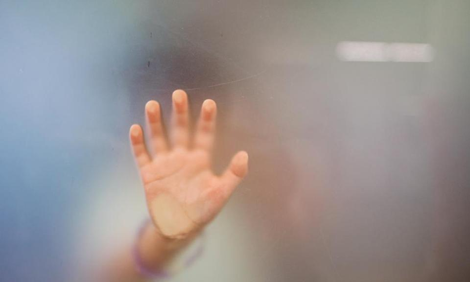 Close up of little girl's hand against glass