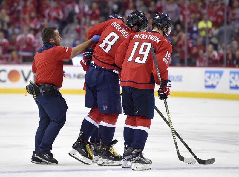Washington Capitals left wing Alex Ovechkin (8), of Russia, is helped off the ice by a trainer and Nicklas Backstrom (19), of Sweden, after he was injured during the first period of Game 5 in an NHL Stanley Cup hockey first-round playoff series against the Toronto Maple Leafs, Friday, April 21, 2017, in Washington. (AP Photo/Nick Wass)