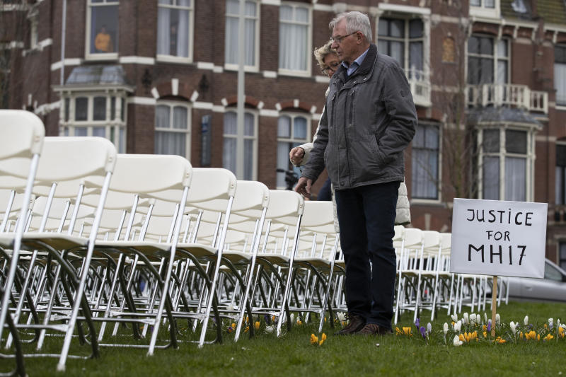 Relatives walk along 298 empty chairs, each chair for one of the 298 victims of the downed Malaysia Air flight MH17, are placed in a park opposite the Russian embassy in The Hague, Netherlands, Sunday, March 8, 2020. A missile fired from territory controlled by pro-Russian rebels in Ukraine in 2014, tore the MH17 passenger jet apart killing all 298 people on board. United by grief across oceans and continents, families who lost loved hope that the trial which starts Monday March 9, 2020, will finally deliver them something that has remained elusive ever since: The truth. (AP Photo/Peter Dejong )