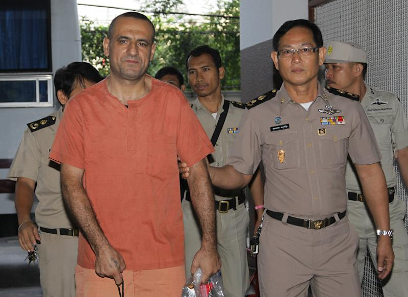 Lebanese-Swedish Atris Hussein, front left, is escorted by Thai officers upon his arrival at criminal court in Bangkok, Thailand Wednesday, March 21 , 2012. Hussein was detained for illegally possessing explosive materials. His arrest in last January was linked to U.S. and Israeli warnings of a possible terror threat in Bangkok. (AP photo/Sakchai Lalit)