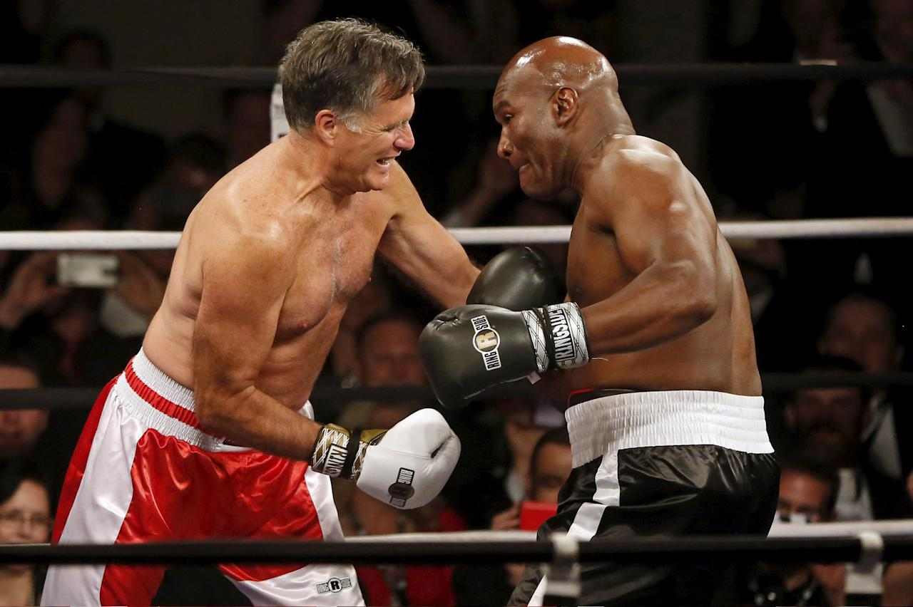 Former Massachusetts Governor and two-time presidential candidate Mitt Romney (L) fights five-time heavyweight champion Evander Holyfield during their boxing match in Salt Lake City, Utah May 15, 2015. The two boxed to benefit the medical charity CharityVision. REUTERS/Jim Urquhart