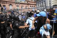 Soccer fans scuffle with police guarding the presidential palace, where Diego Maradona is lying in state, in Buenos Aires, Argentina, Thursday, Nov. 26, 2020. The Argentine soccer great who was among the best players ever and who led his country to the 1986 World Cup title died from a heart attack at his home Wednesday, at the age of 60. (AP Photo/Rodrigo Abd)