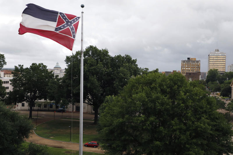A Mississippi state flag flies outside the Capitol in Jackson, Miss., Thursday, June 25, 2020. Athletic coaches and their staffs from the state's public universities held a joint news conference and called for a change in the Mississippi state flag. Additionally, several head coaches met with both the lieutenant governor and Speaker Philip Gunn, as well as their lawmakers, to lobby for the change. The current flag has in the canton portion of the banner the design of the Civil War-era Confederate battle flag, that has been the center of a long-simmering debate about its removal or replacement. (AP Photo/Rogelio V. Solis)