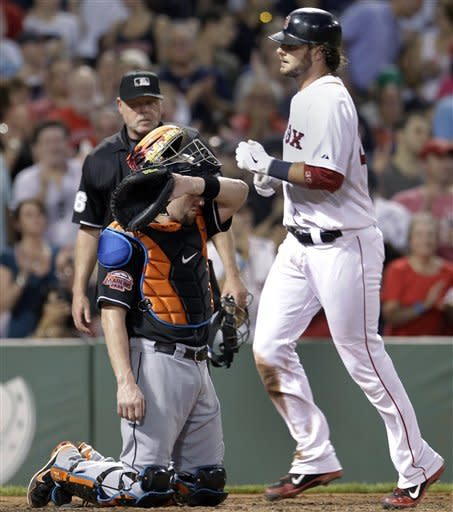 Miami Marlins catcher John Buck wipes his face as Boston Red Sox's Jarrod Saltalamacchia crosses home plate with a solo home run during the fourth inning of an interleague baseball game at Fenway Park in Boston on Wednesday, June 20, 2012. (AP Photo/Elise Amendola)