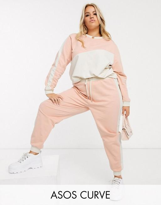 """<p><strong>Asos Curve</strong></p><p>us.asos.com</p><p><strong>$54.00</strong></p><p><a href=""""https://go.redirectingat.com?id=74968X1596630&url=https%3A%2F%2Fwww.asos.com%2Fus%2Fasos-curve%2Fasos-design-curve-tracksuit-color-blocked-sweat-jogger%2Fprd%2F13956151&sref=https%3A%2F%2Fwww.cosmopolitan.com%2Fstyle-beauty%2Fg31939434%2Fbest-sweatsuit-sets%2F"""" target=""""_blank"""">Shop Now</a></p><p>Throw on this long-sleeve crewneck and matching pants the next time you head to Club Living Room.</p>"""