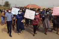 Nurses and supporters in Owo, Nigeria, participate in a march on Feb. 7, 2021, demanding the Federal Medical Centre in Owo provide security for its staff after two nurses were were attacked by the family of a deceased COVID-19 patient. A new report identified hundreds of threats or acts of violence against health care workers and facilities last year linked to fear or frustration around the coronavirus. (Tochukwu Q.O. via AP)