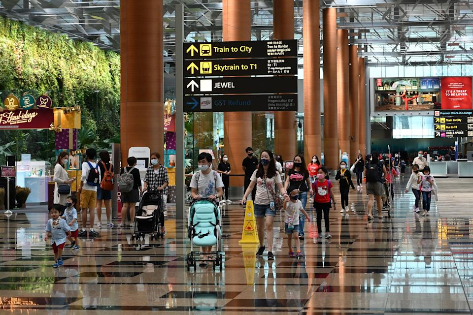 Visitors walk through a terminal of the Changi International Airport in Singapore on December 7, 2020. (Photo by Roslan RAHMAN / AFP) (Photo by ROSLAN RAHMAN/AFP via Getty Images)