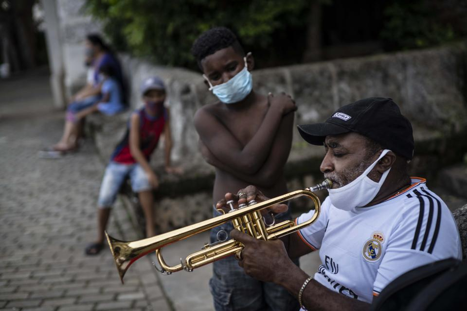 Wearing a face mask amid the new coronavirus pandemic, a child watches trumpeter Carlos Sanchez practices in preparation for tourist arrivals in Old Havana, Cuba, Tuesday, Oct. 27, 2020. A Trump reelection would likely spell another four years of tightened U.S. sanctions while many expect a Biden administration to carry out at least some opening. Cubans on island, caught in between the six-decade debacle, said they know little about Biden but want to see Trump out of the White House. (AP Photo/Ramon Espinosa)