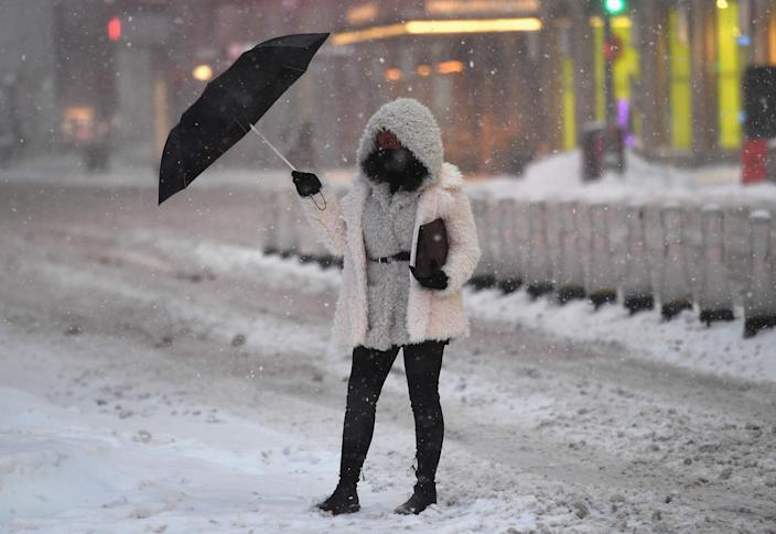 A woman holds an umbrella in Times Square during a winter storm on Feb. 1, 2021 in New York City.
