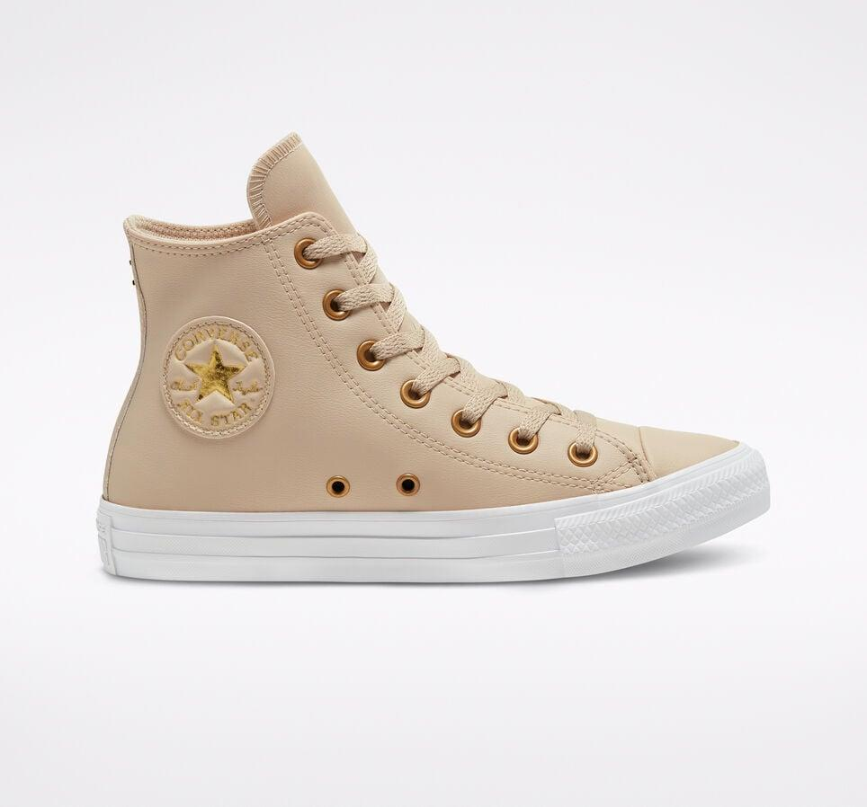 """<p>I love the gold hardware and monochromatic look of these brand-new <product href=""""https://www.converse.com/shop/p/faux-leather-chuck-taylor-all-star-womens-high-top-shoe/568660C.html?dwvar_568660C_color=farro%2Fgold%2Fwhite&amp;styleNo=568660C&amp;cgid=womens-shoes"""" target=""""_blank"""" class=""""ga-track"""" data-ga-category=""""internal click"""" data-ga-label=""""https://www.converse.com/shop/p/faux-leather-chuck-taylor-all-star-womens-high-top-shoe/568660C.html?dwvar_568660C_color=farro%2Fgold%2Fwhite&amp;styleNo=568660C&amp;cgid=womens-shoes"""" data-ga-action=""""body text link"""">Converse Faux Leather Chuck Taylor All Star Sneakers</product> ($65).</p>"""