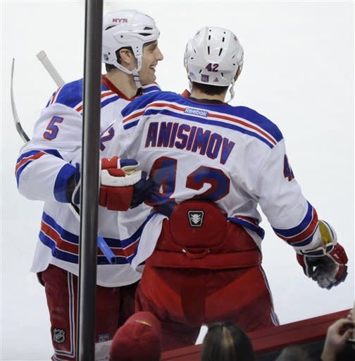 New York Rangers' Artem Anisimov , right, of Russia, celebrates with teammate Dan Girardi, left, after scoring against the Chicago Blackhawks during the first period of an NHL hockey game in Chicago, Friday, March 9, 2012. (AP Photo/Paul Beaty)