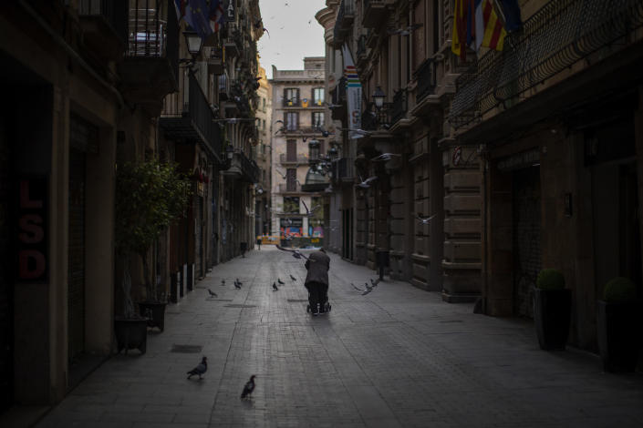 A woman pushes a cart with her belongings as she walks along an empty street in downtown Barcelona, Spain, March 21, 2020. The image was part of a series by Associated Press photographer Emilio Morenatti that won the 2021 Pulitzer Prize for feature photography. (AP Photo/Emilio Morenatti)