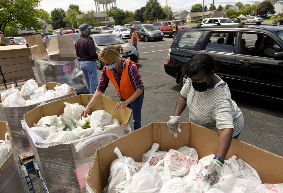 """Muhlenberg, PA - May 21: From left Robin Eckert, and Diane Benson, get food to put in peoples cars. At the Good Shepherd Evangelical Lutheran Church in Muhlenberg township Thursday afternoon May 21, 2020 where Helping Harvest held a """"pop-up"""" food distribution as a drive-through pickup. The church normally holds a monthly Muhlenberg Area Churches Food Pantry, but haven't recently because of concerns about coronavirus.  (Photo by Ben Hasty/MediaNews Group/Reading Eagle via Getty Images)"""