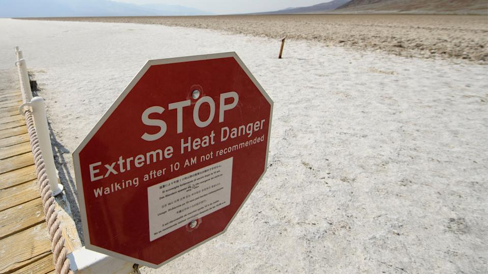 A sign warns of extreme heat danger at the salt flats of Badwater Basin inside Death Valley National Park in California on June 17. (Patrick T. Fallon/AFP via Getty Images)