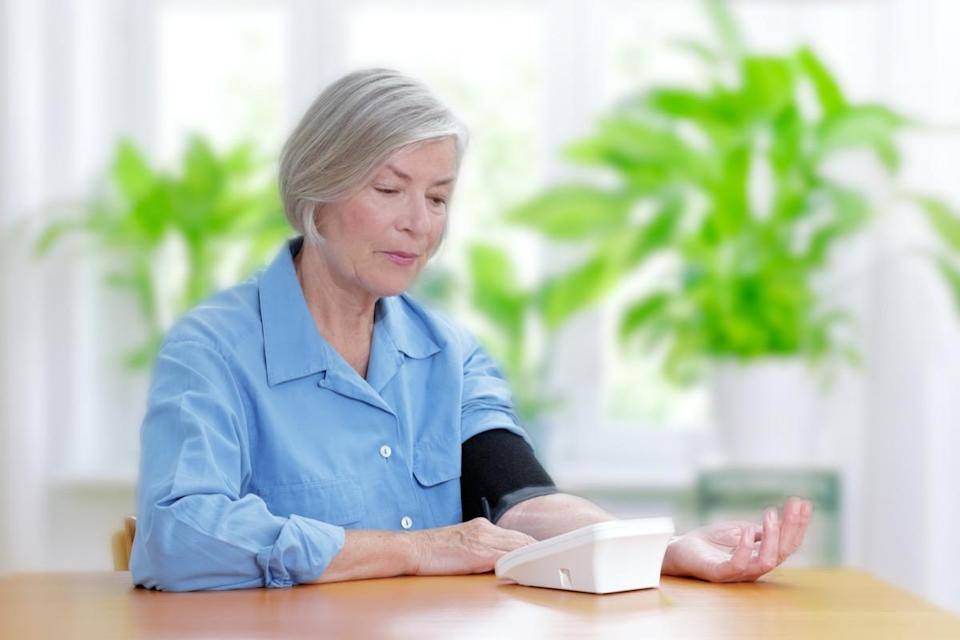 Senior woman suffering from high blood pressure sitting at a table in her living room using a blood pressure monitor