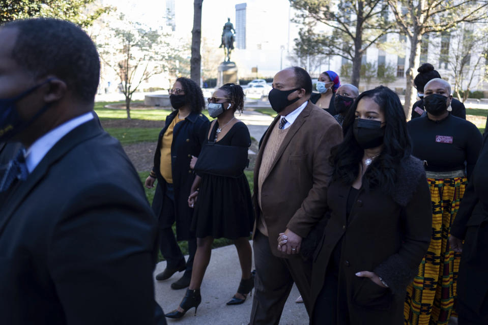 FILE - In this Monday, March 29, 2021 file photo, Georgia State Rep. Park Cannon, D-Atlanta,, center with arm in sling, walks beside Martin Luther King, III, as she returns to the State Capitol in Atlanta after being arrested last week for knocking on the governor's office door as he signed voting legislation. In Georgia, faith leaders are asking corporate executives to condemn laws restricting voting access — or face a boycott. In Arizona and Texas, clergy have assembled outside the state capitols to decry what they view as voter-suppression measures targeting Black and Hispanic people.(AP Photo/Ben Gray)