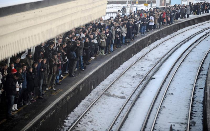 Commuters wait for a train in a snow-covered Clapham Junction  - Reuters