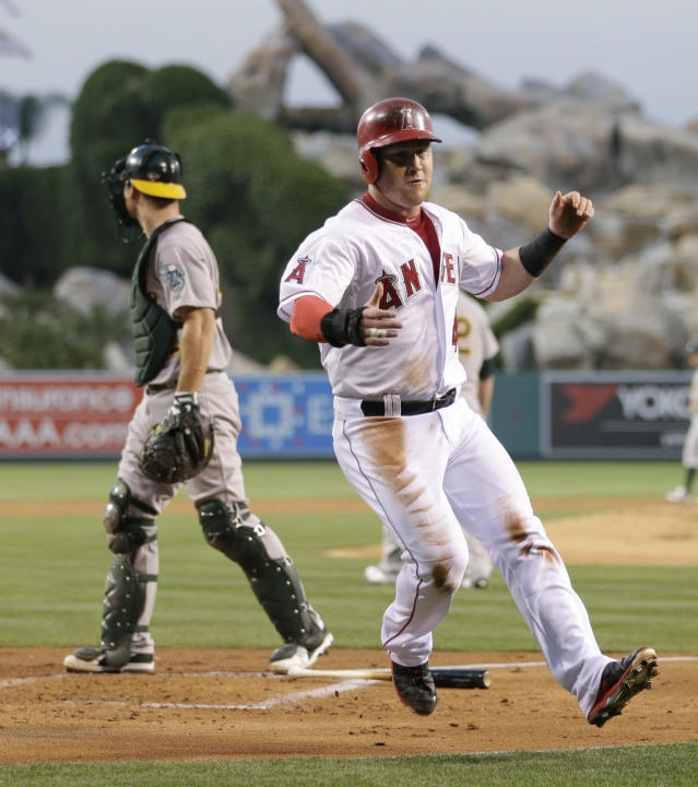 Los Angeles Angels' Kole Calhoun celebrates after scoring on a double by Mike Trout during the first inning of a baseball game against the Oakland Athletics on Tuesday, April 15, 2014, in Anaheim, Calif. (AP Photo/Jae C. Hong)