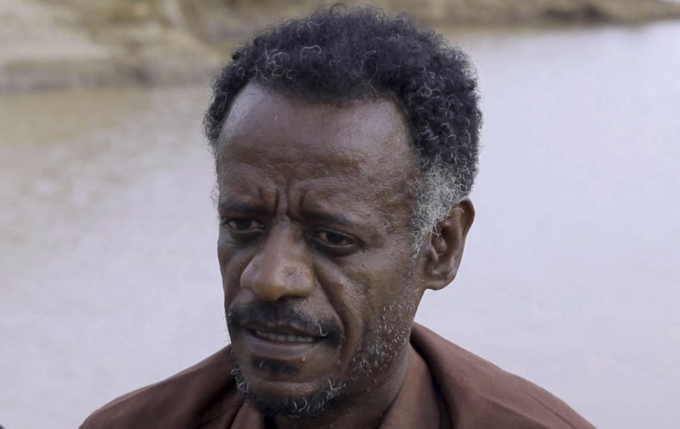 Dr. Tewodros Tefera, an Ethiopian refugee doctor who has been documenting the arrival of the bodies and their injuries, is interviewed beside the Setit river at Wad el Hilu, Sudan on Wednesday, Aug. 4, 2021. Dozens of bodies have been found floating down the Setit River, known in Ethiopia as Tekeze River, in southwestern Sudan in the past week. (AP Photo/Mohaned Awad)