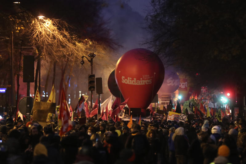 People march during a demonstration in Paris, Thursday, Dec. 5, 2019. The Eiffel Tower shut down, France's high-speed trains stood still and tens of thousands of people marched through Paris and other cities Thursday, in a massive and sometimes chaotic outpouring of anger at the government's plan to overhaul the retirement system. (AP Photo/Thibault Camus)