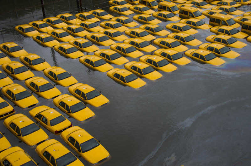 FILE - In this Oct. 30, 2012 file photo, a parking lot full of yellow cabs in Hoboken, N.J. is flooded as a result of Superstorm Sandy. Global warming is rapidly turning America the beautiful into America the stormy, sneezy and dangerous, according to the National Climate Assessment report released Tuesday, May 6, 2014. (AP Photo/Charles Sykes, File)
