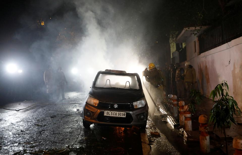 Firefighters douse a car after demonstrators set it on fire during a protest against a new citizenship law in Delhi, India, December 20, 2019. REUTERS/Adnan Abidi