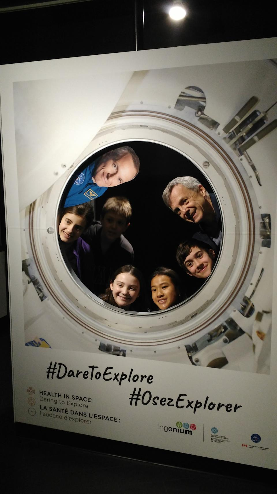 Former Canadian astronaut Robert Thirsk (top right) poses with schoolchildren at a new museum exhibit at the Canada Aviation and Space Museum in Ottawa on Feb. 7, 2019. The exhibit highlights the contributions of medical space technology to astronaut and consumer health. It also features astronaut doctors such as David Saint-Jacques. A flat picture of Saint-Jacques is displayed at top left. <cite>Elizabeth Howell</cite>