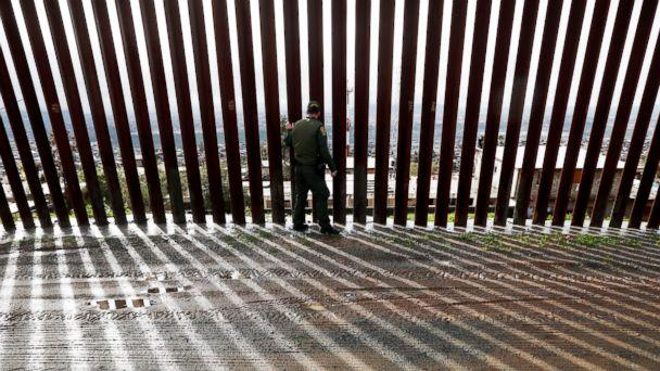 PHOTO: Border Patrol agent Vincent Pirro touches a section of the border wall separating Tijuana, Mexico, behind, from San Diego, Feb. 5, 2019, in San Diego. (Gregory Bull/AP)