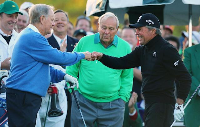 Arnold Palmer, center, watches as Jack Nicklaus, left, and Gary Player touch fists after Palmer hit his ceremonial drive on the first tee during the first round of the Masters golf tournament Thursday, April 10, 2014, in Augusta, Ga. (AP Photo/Atlanta Journal-Constitution, Curtis Compton)
