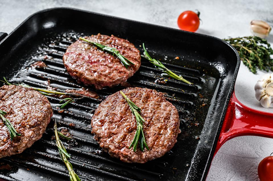 Beef burger patties sizzling on a hot barbecue pan. White background. Top view.