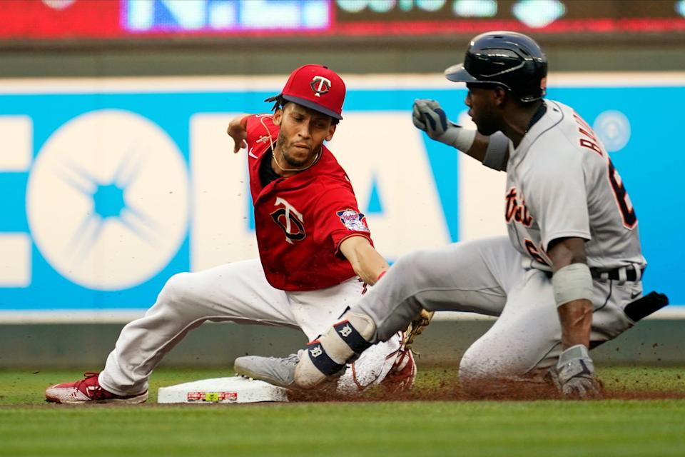 Detroit Tigers' Akil Baddoo, right, beats the tag by Minnesota Twins shortstop Andrelton Simmons for a double during the first inning of a baseball game, Tuesday, July 27, 2021, in Minneapolis.