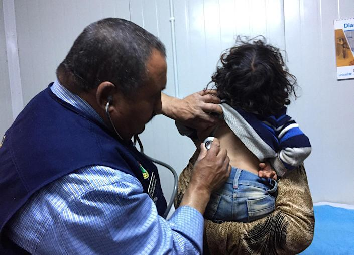 In this Wednesday, March 1, 2017 photo, a doctor examines a three-year-old Syrian girl at a U.N. mobile clinic set up near a makeshift tent camp for tens of thousands of war-displaced Syrians stranded in the desert on Jordan's border. U.N. agencies are ramping up aid delivery to tens of thousands of war-displaced Syrians stuck in the desert on Jordan's sealed border, after months of being denied access. Yet harsh weather and anxious crowds often disrupt one of the U.N.'s most complex missions anywhere. (AP Photo/Karin Laub)