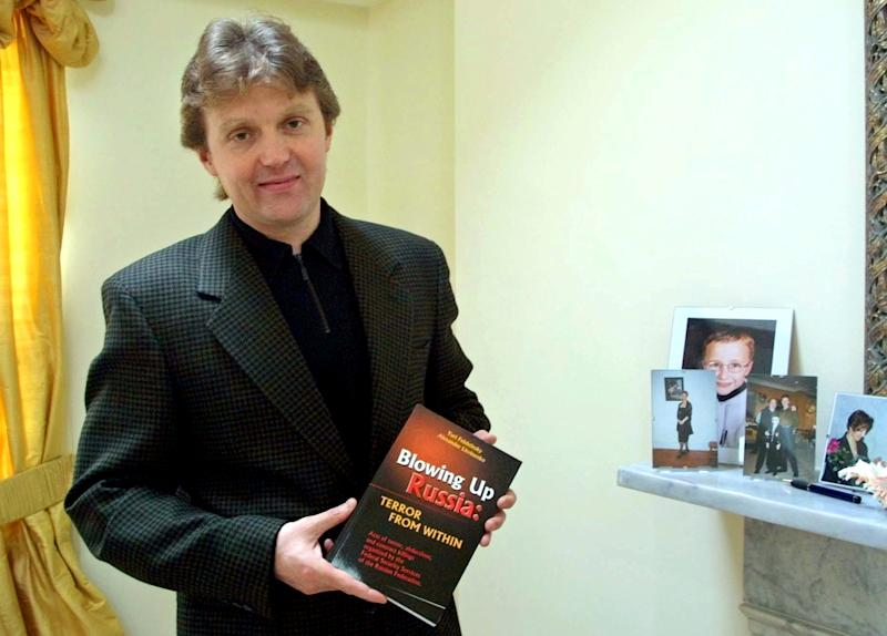 "FILE - A Friday, May 10, 2002 file photo showing Alexander Litvinenko, former KGB spy and author of the book ""Blowing Up Russia: Terror From Within"" photographed at his home in London. A coroner overseeing a British inquest into the 2006 poisoning death of Alexander Litvinenko has requested a public inquiry to be held so that crucial evidence can be scrutinized. Coroner Robert Owen's request to Justice Secretary Christopher Grayling Wednesday, June 5, 2013,  followed a ruling last month stating that sensitive evidence _ including documents relating to Russia's alleged role in the agent's death _ has to be excluded from the existing inquest. The ruling was made after British Foreign Secretary William Hague applied to the inquest to keep some evidence surrounding the case secret on national security grounds. Litvinenko, a 43-year-old former agent turned Kremlin critic, died in November 2006, after drinking tea laced with the radioactive isotope polonium-210 at a London hotel. (AP Photo/Alistair Fuller, File)"