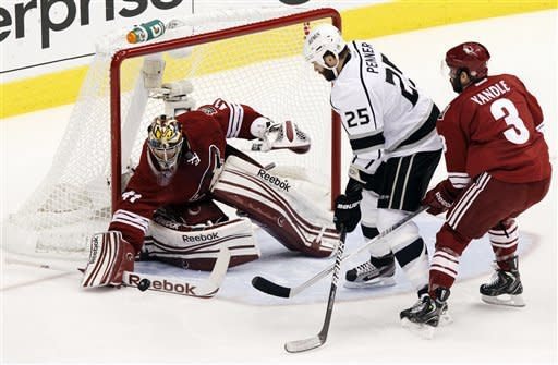 Phoenix Coyotes goalie Mike Smith (41) stops a shot on goal by Los Angeles Kings left wing Dustin Penner (25) as Coyotes' Keith Yandle (3) defends during the first period of Game 2 of the NHL hockey Stanley Cup Western Conference finals, Tuesday, May 15, 2012, in Glendale, Ariz. (AP Photo/Ross D. Franklin)