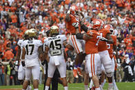 Clemson's Travis Etienne (9) is lifted while celebrating a touchdown with Sean Pollard (76) during the first half of an NCAA college football game against Wake Forest, Saturday, Nov. 16, 2019, in Clemson, S.C. (AP Photo/Richard Shiro)